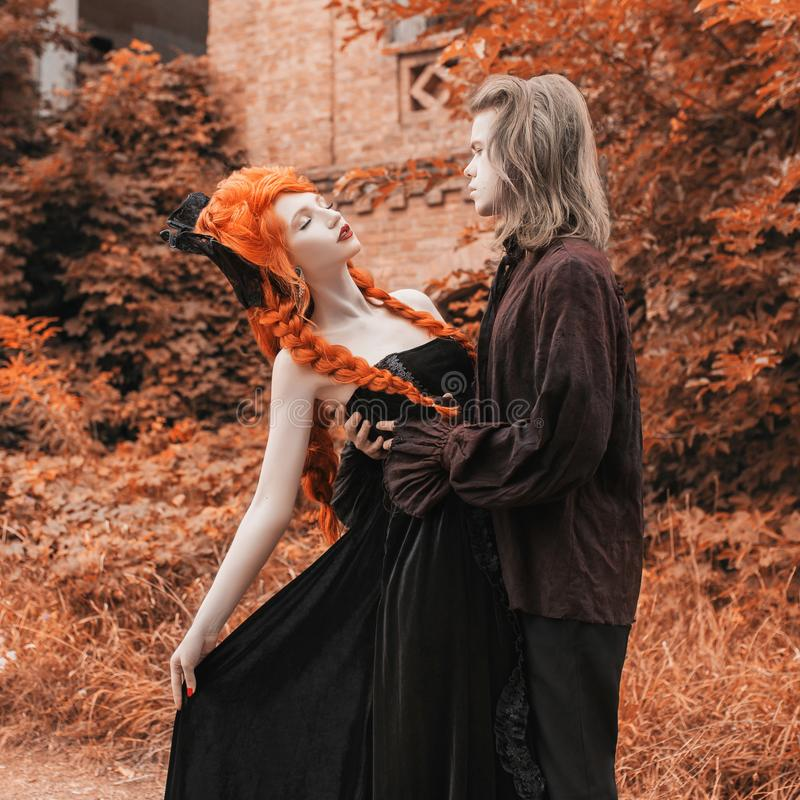 Gothic couple dance in halloween clothes. Pale victorian vampire in renaissance dress. Gothic costume for halloween party. Vampire. Couple on dark background stock image