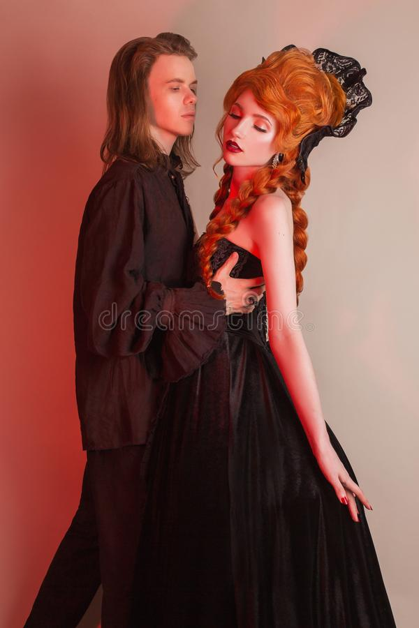 Gothic couple dancing in halloween clothes. Pale victorian vampire in carnival dress. Gothic costume for halloween party. Vampire stock photo