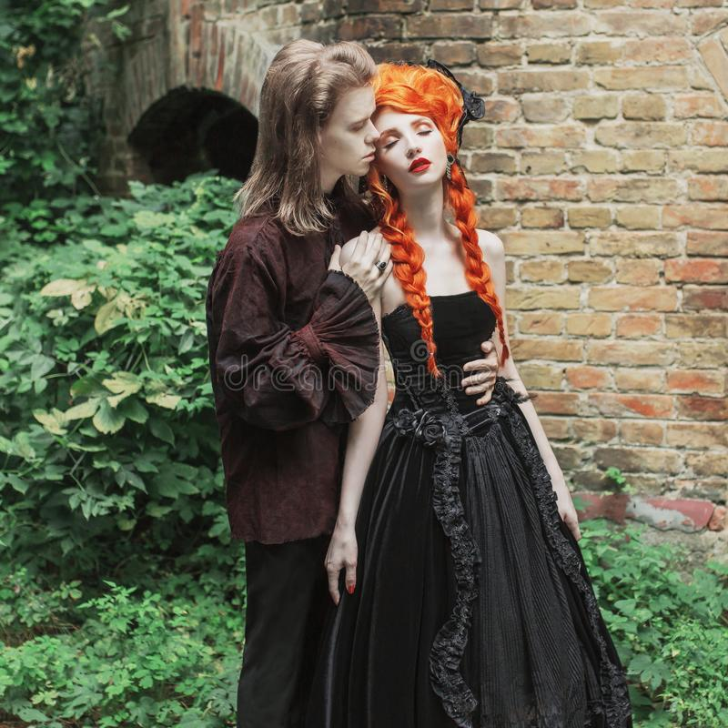 Gothic couple embracing in halloween costume. Vampire in victorian clothes. Redhead woman in black wedding dress. Clothes for hall stock photo