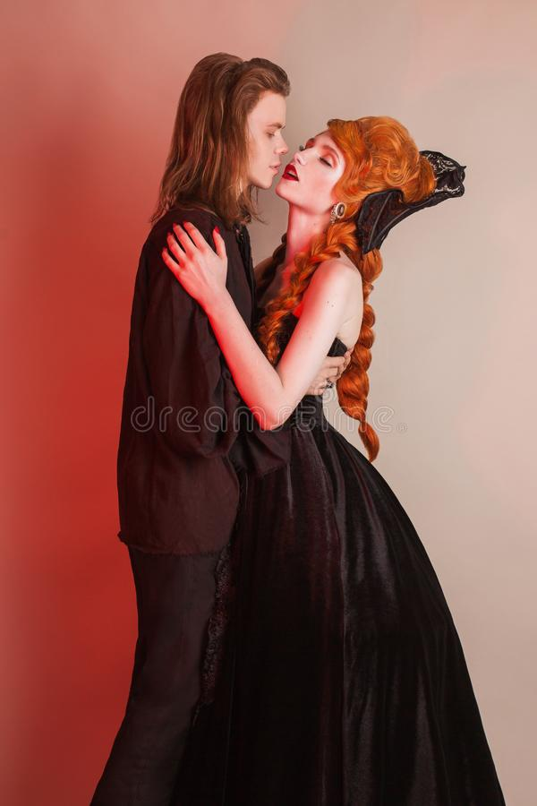 Gothic couple in halloween clothes. Woman temptation. Vampire in renaissance dress. Gothic costume for halloween. Sweetheart couple on dark. Girl in royalty free stock photo