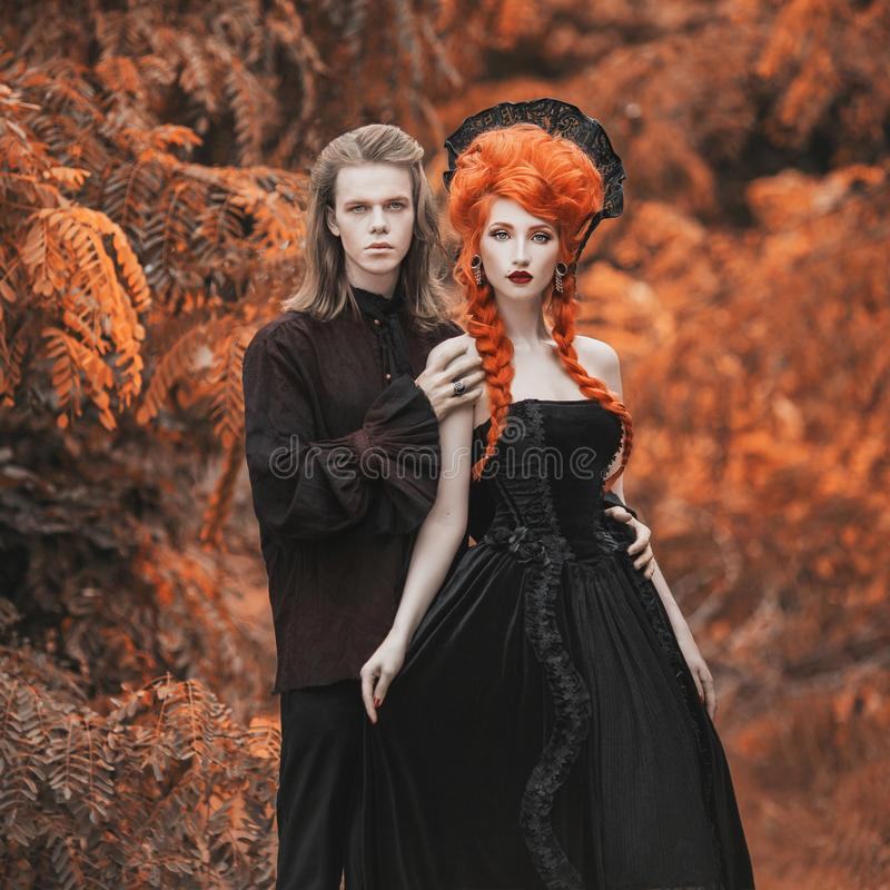 Gothic couple in halloween costume. Gloomy vampire in victorian clothes. Redhead woman vampire in black victorian dress. Gothic cl stock photography