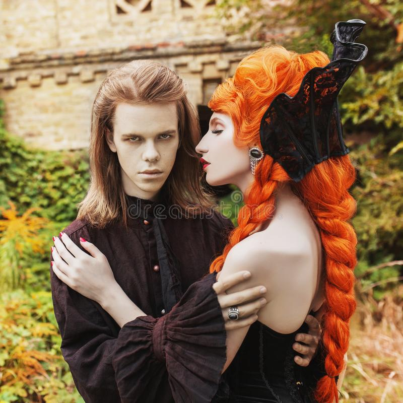 Gothic couple in a halloween costume. Pale undead vampire in dark victorian clothes. Redhead woman in black carnival dress. royalty free stock images