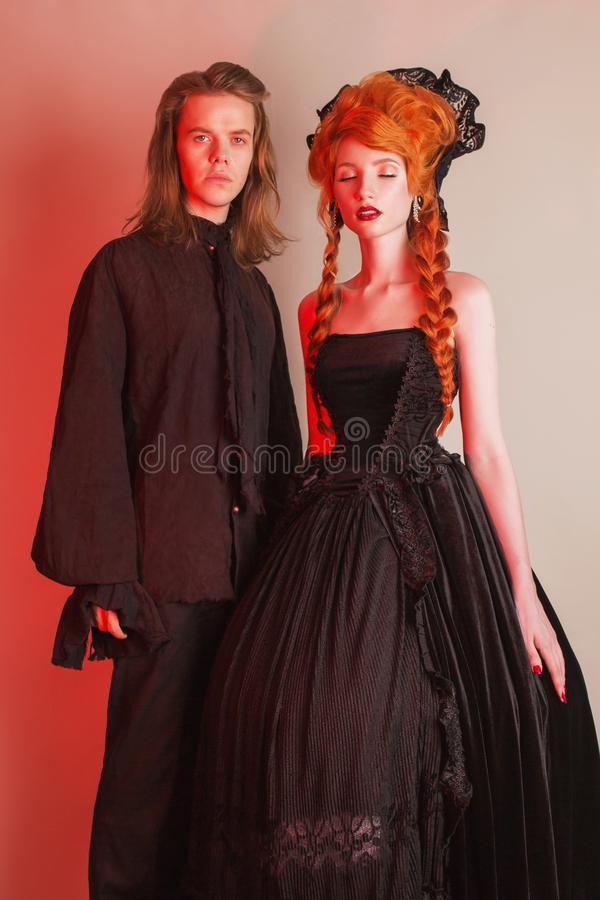 Gothic couple in halloween costume. Pale undead vampire in edwardian carnival clothes. Gothic costume for halloween party. Redhead women in black carnival royalty free stock image
