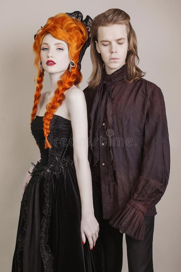 Gothic couple in halloween costume. Pale undead vampire in edwardian carnival clothes. Gothic costume for halloween party. Redhead women in black carnival stock images