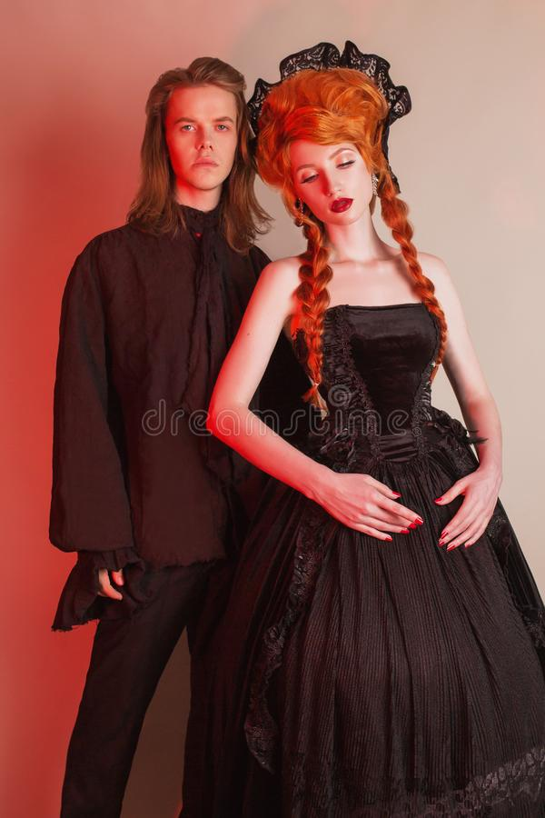Gothic couple in halloween costume. Pale undead vampire in edwardian carnival clothes. Gothic costume for halloween party. stock images