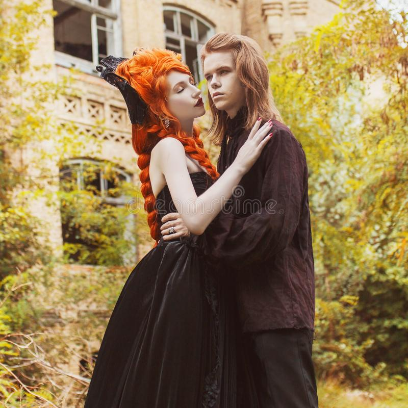 Gothic couple in a halloween costume. Pale undead vampire in edwardian clothes. Gothic clothes for halloween party. Redhead woman stock images