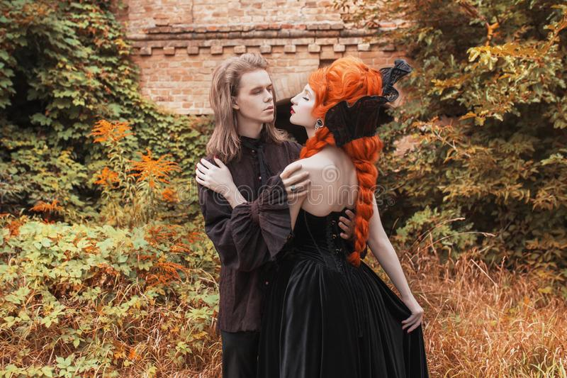 Gothic couple in a halloween costume. Pale undead vampire in edwardian clothes. Punk couple on autumn background. Gothic clothes f stock images