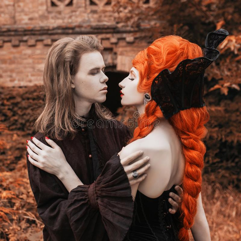 Gothic couple in halloween costume. Pale undead vampire in victorian clothes. Redhead woman vampire in black victorian dress. Gothic couple in halloween costume royalty free stock photography