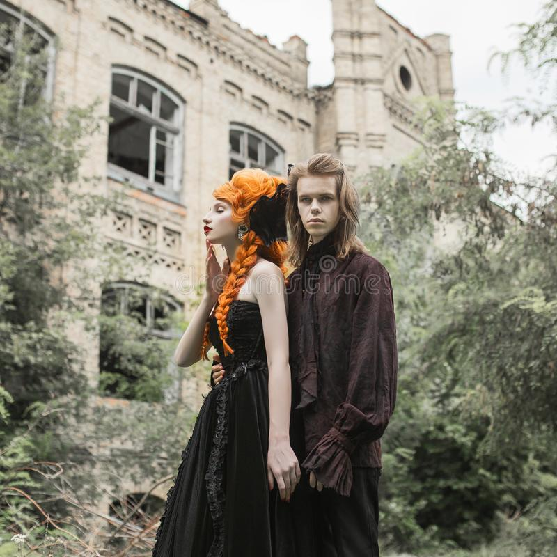Gothic couple in a halloween costume. Pale undead vampires in dark medieval clothes. Gothic clothes for halloween party. Redhead women in black medieval dress royalty free stock images