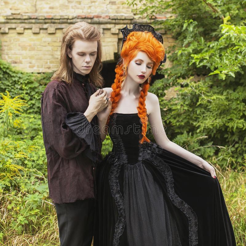 Gothic couple in a halloween costume. Pale undead vampires in dark victorian clothes. Redhead woman in black carnival dress. stock image