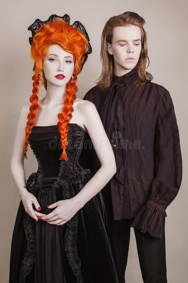 Gothic couple in a halloween costume. Pale undead vampires in dark victorian clothes. Redhead woman in black carnival dress. royalty free stock image
