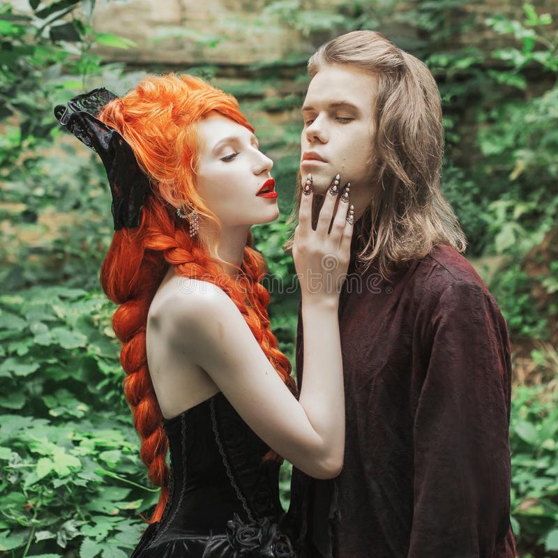 Gothic couple in halloween costume. Vampire in victorian clothes. Redhead woman dominant in black dress. Gothic clothes for hallow. Gothic couple in halloween stock photos