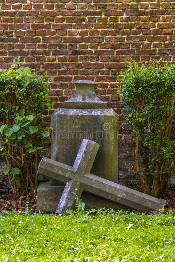 Gothic cross and tomb in cemetery at Saint-Hubert church, Aubel. A gothic cross and tomb in cemetery at Saint-Hubert church, Aubel stock images