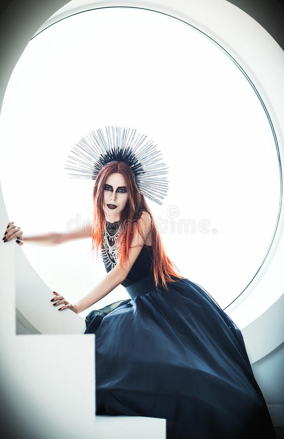 Gothic fashion: beautiful young girl in black dress and headwear sitting against round window stock photography