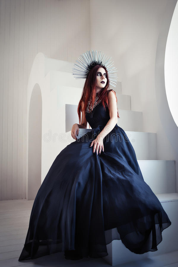 Gothic fashion: beautiful young girl in black dress and headwear sitting on staircase stock photo