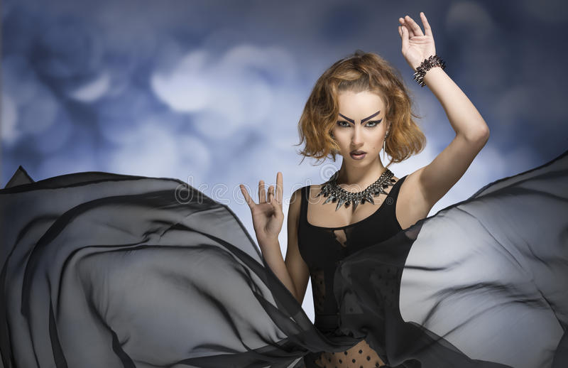 Gothic fashion woman. Very girl with bizarre gothic make-up, style and accessories posing in fashion portrait with long veil flying skirt. Carnival look stock photos
