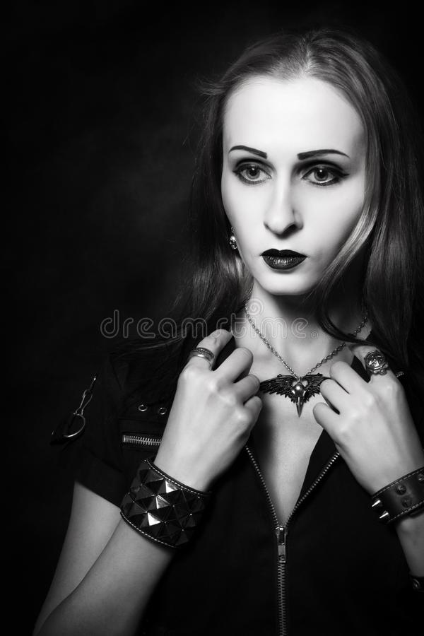 Redhead gothic girl. Gothic girl in dark clothes posing over dark background royalty free stock photography