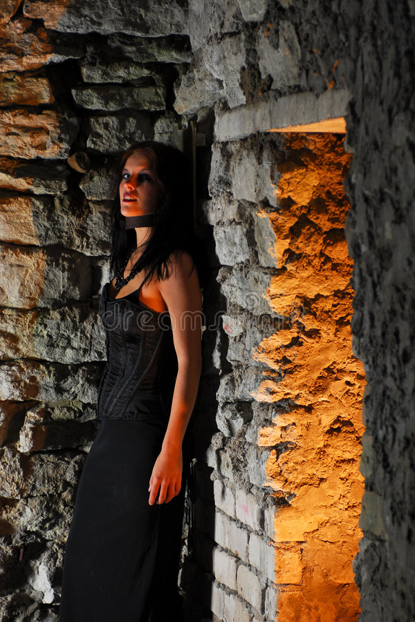 Gothic girl in a dungeon royalty free stock photography