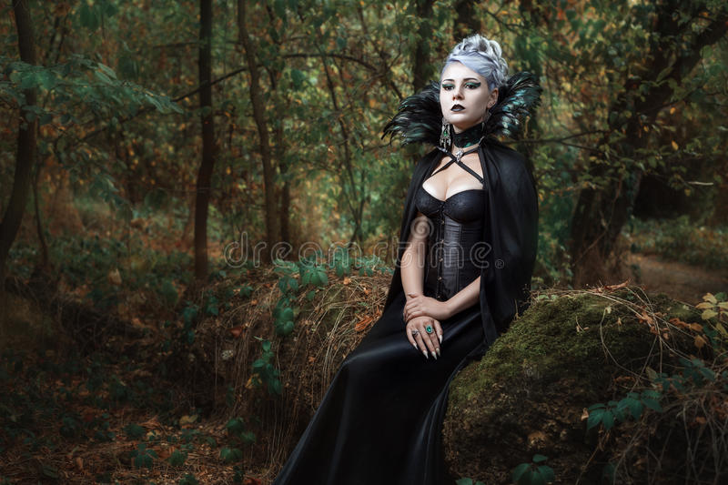 Gothic girl in the forest. Gothic girl in black raincoat sits on a tree in the forest royalty free stock photography