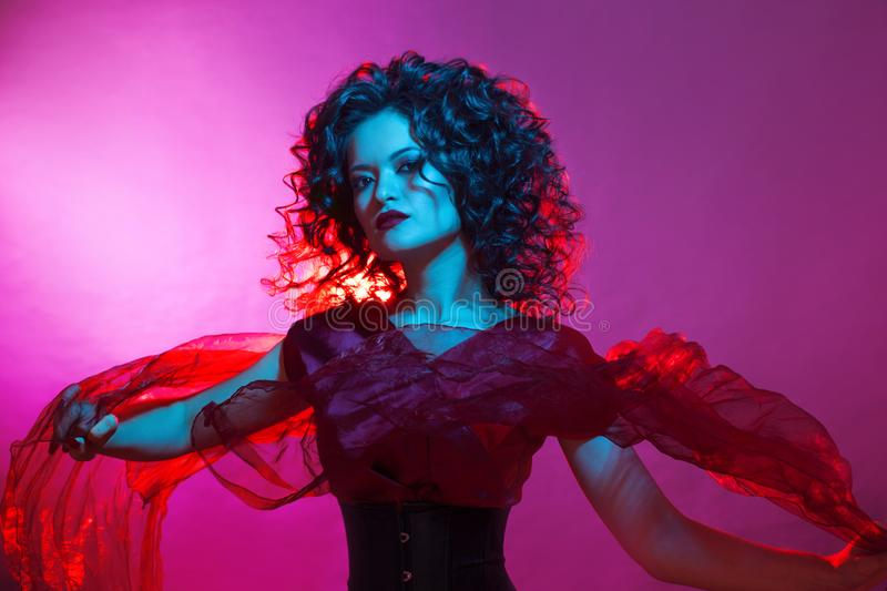 Gothic girl in red. Dancing young woman. Gothic girl in red. Dancing young femme fatale. Neon light, Halloween party royalty free stock image
