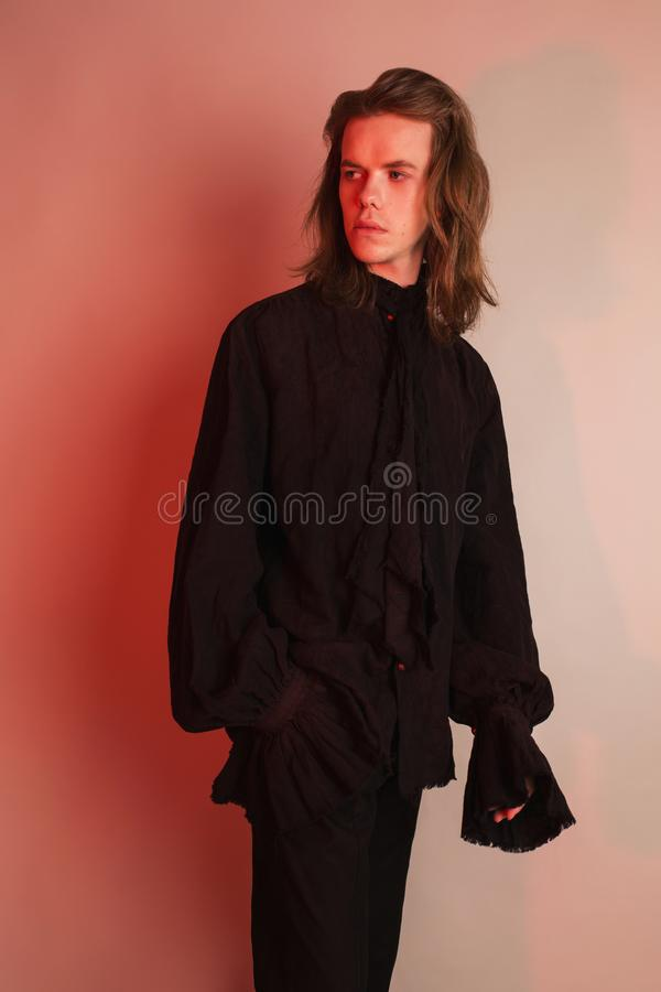 Gothic halloween clothes. Medieval prince with hairstyle. Punk with long hair. Undead knight. Vampire man with hairdo. Spooky outf stock image