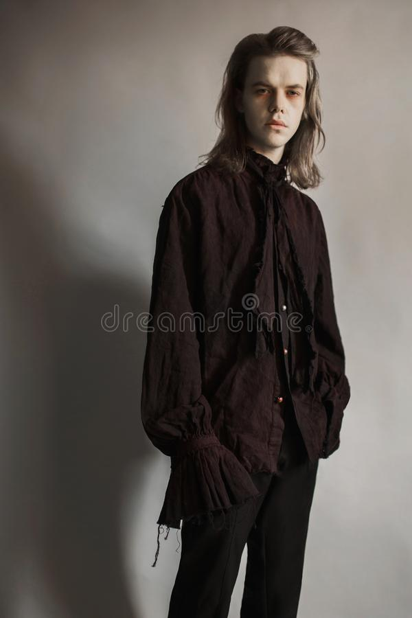 Gothic halloween clothes. Mystical knight. Prince with hairstyle. Punk with long hair. Vampire man with hairdo. Mystical outfit fo royalty free stock photography