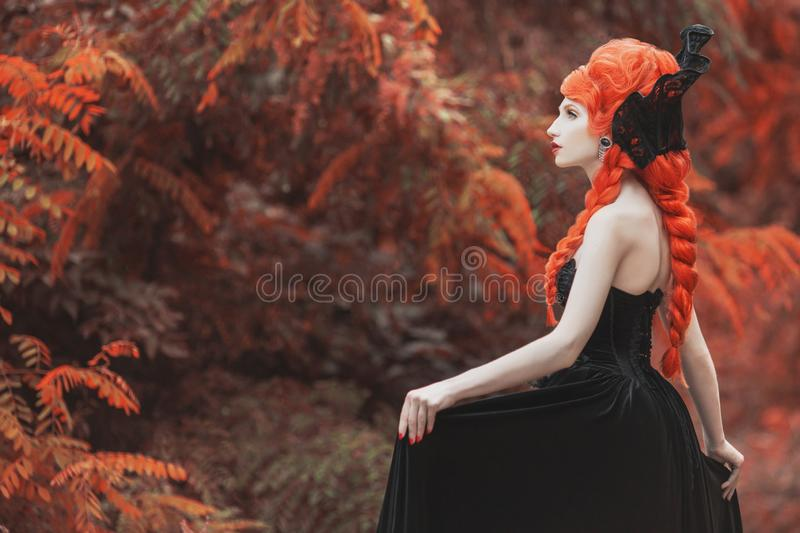 Gothic halloween clothes. Young edwardian redhead queen with hairstyle. Princess with red hair. Mystical queen in gothic dress. Vampire woman with pale skin royalty free stock photography