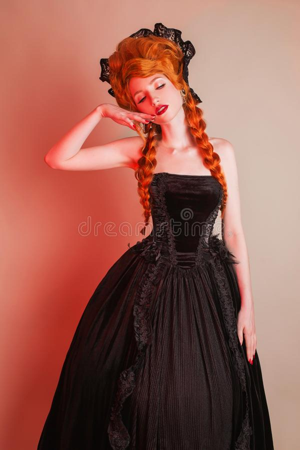 Gothic halloween clothes. Young fantastic redhead queen with hairstyle. Princess with red hair. Vampire with pale skin. Mystical o. Utfit for halloween party royalty free stock images