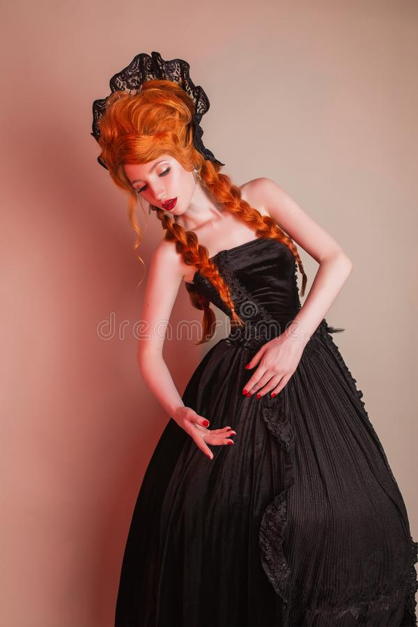 Gothic halloween clothes. Young fantasy redhead queen with hairstyle. Princess with red hair. Vampire with pale skin. Mystical out. Fit for halloween party royalty free stock photography