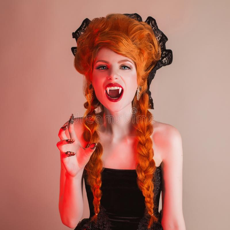 Gothic halloween clothes. Young terrible redhead queen with hairstyle. Demon with red hair. Vampire with sharp fangs. stock photos