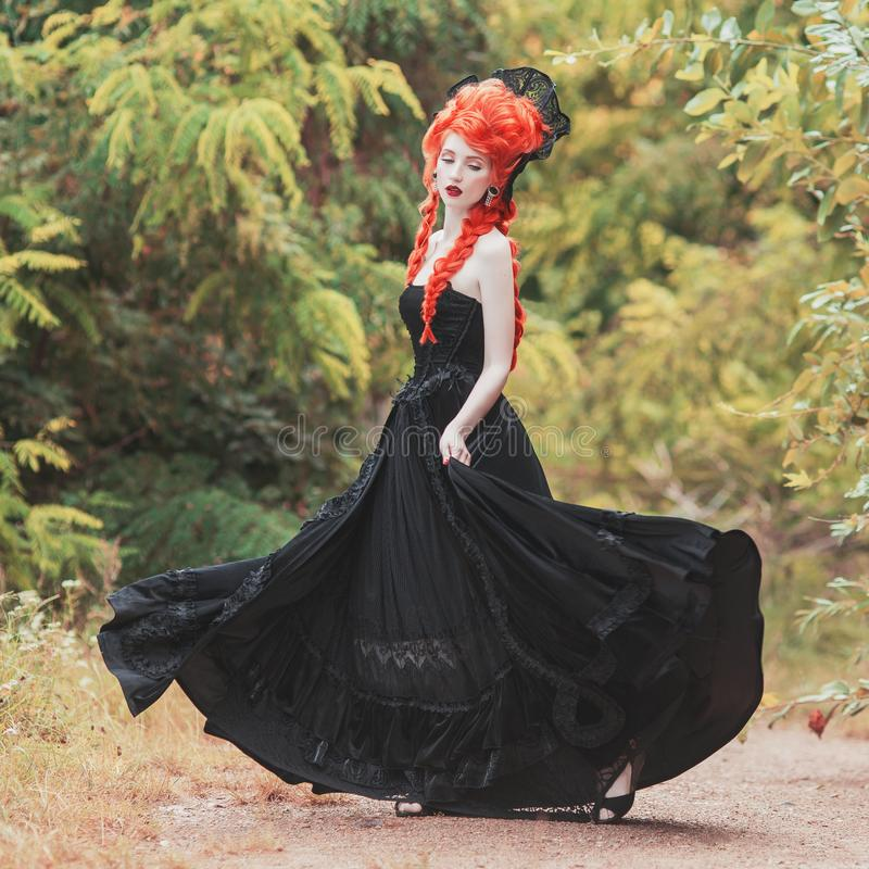 Gothic halloween clothes. Young victorian redhead queen with hairstyle. Lady with red hair. Vampire with pale skin. Victorian outf. It for halloween party royalty free stock photography