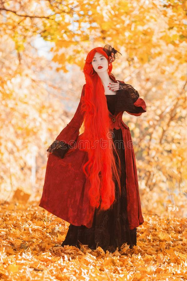 Gothic halloween coat. Fairy cosplay. Young medieval queen on autumn background. Lady with red hair. Vampire with pale skin. stock photography