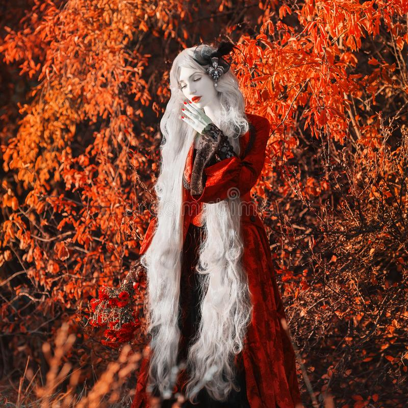 Gothic halloween coat. Young medieval blonde queen autumn background. Lady with gray hair. Vampire with pale skin. Outfit for. Halloween. Fantastic queen in royalty free stock image