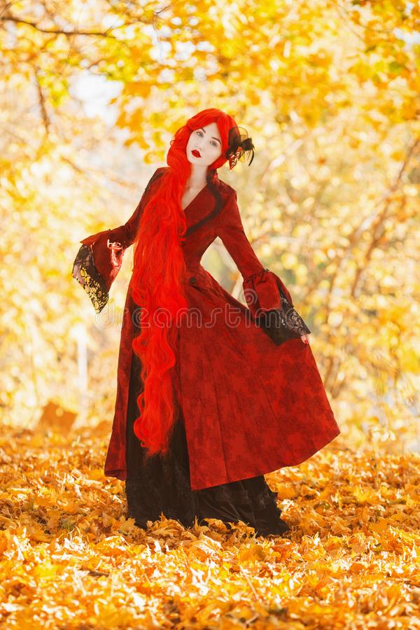 Gothic halloween coat. Young medieval queen on autumn background. Lady with red hair. Vampire with pale skin. Medieval outfit for. Halloween. Fantastic queen royalty free stock photo