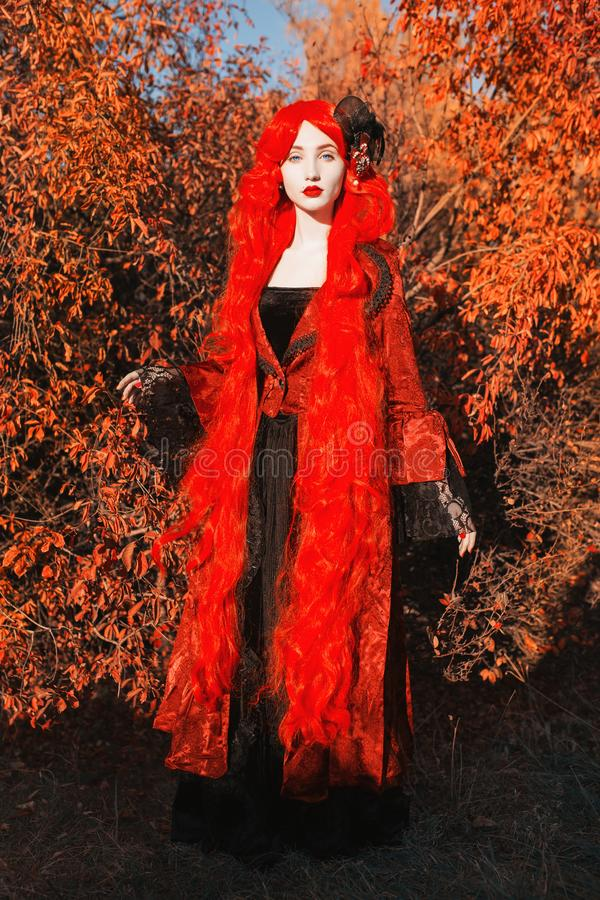 Gothic halloween coat. Young medieval queen on autumn background. Lady with red hair. Vampire with pale skin. Medieval outfit for royalty free stock image