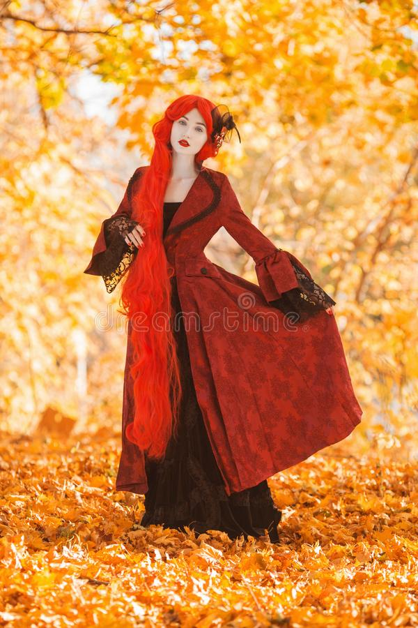Gothic halloween coat. Young medieval queen on autumn background. Lady with red hair. Vampire with pale skin. Medieval outfit for. Halloween. Fantastic queen stock photo