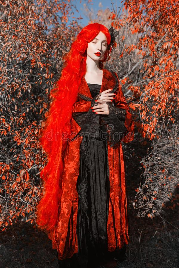Gothic halloween coat. Young medieval queen on autumn background. Lady with red hair. Vampire with pale skin. Medieval outfit for. Halloween. Fantastic queen stock photography
