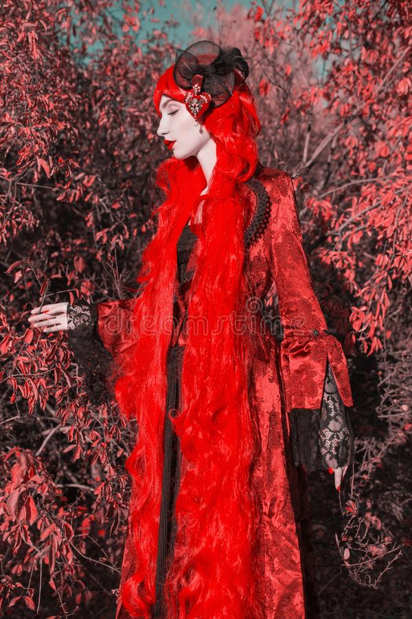 Gothic halloween coat. Young medieval queen on autumn background. Lady with red hair. Vampire with pale skin. Medieval outfit for. Halloween. Fantastic queen royalty free stock images