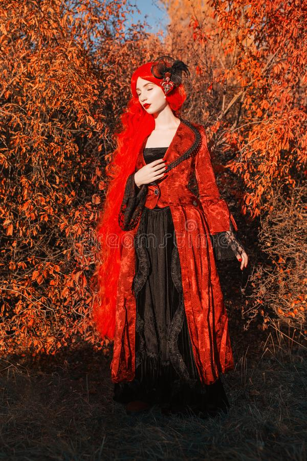 Gothic halloween coat. Young medieval queen on autumn background. Lady with red hair. Vampire with pale skin. Medieval outfit for. Halloween. Fantastic queen royalty free stock photos