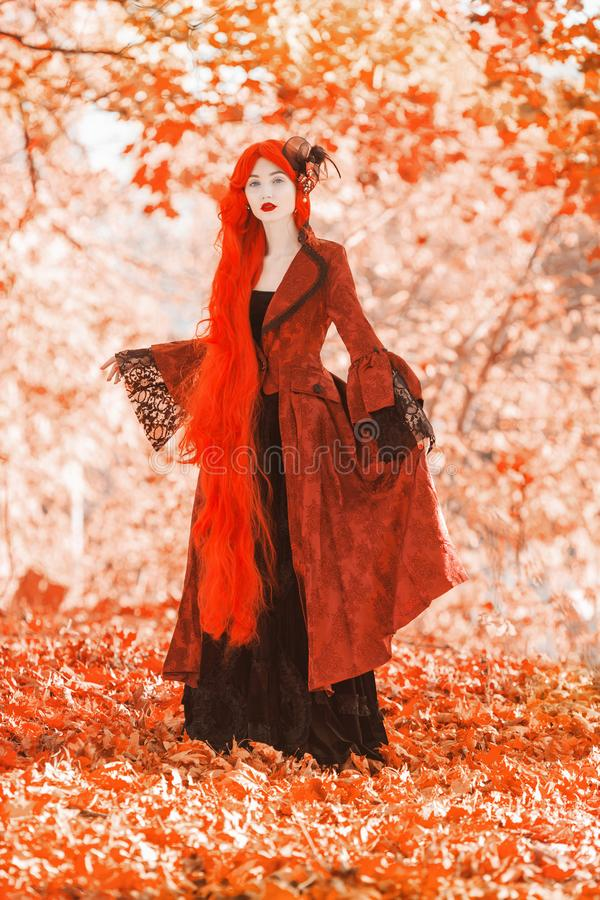 Gothic halloween coat. Young medieval queen on autumn background. Lady with red hair. Vampire with pale skin. Medieval outfit for stock image