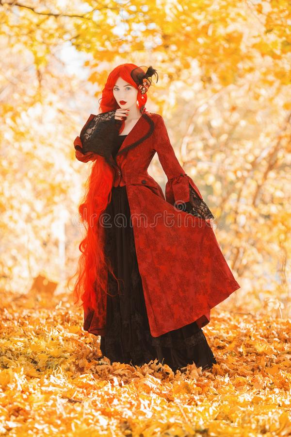 Gothic halloween coat. Young medieval queen on autumn background. Lady with red hair. Yellow foliage. Vampire with pale skin. stock photo