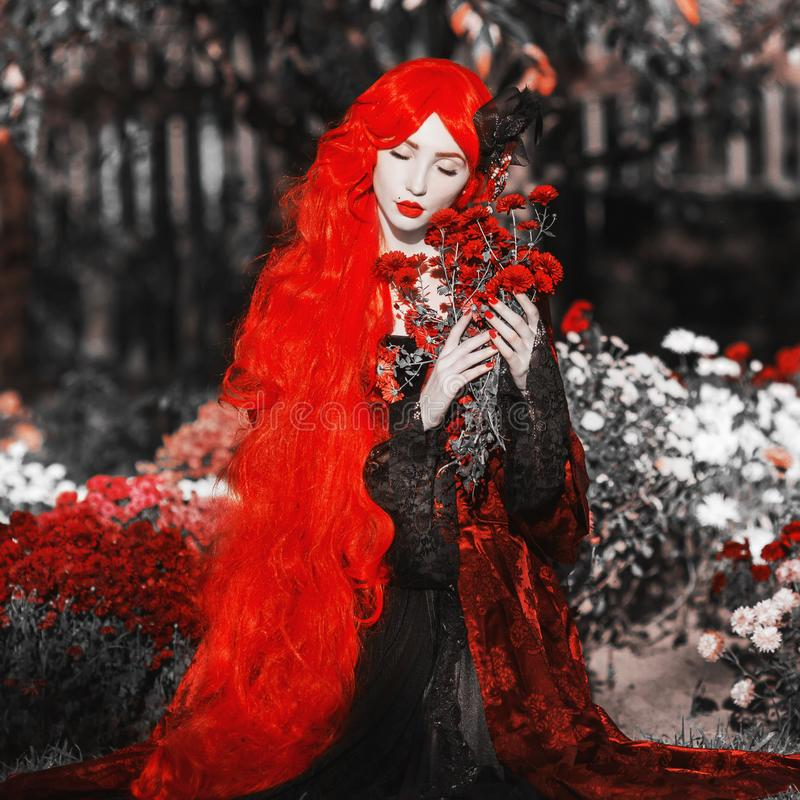 Gothic halloween coat. Young medieval queen with flower bouquet on background of garden. Lady with red hair. Vampire with pale royalty free stock photography