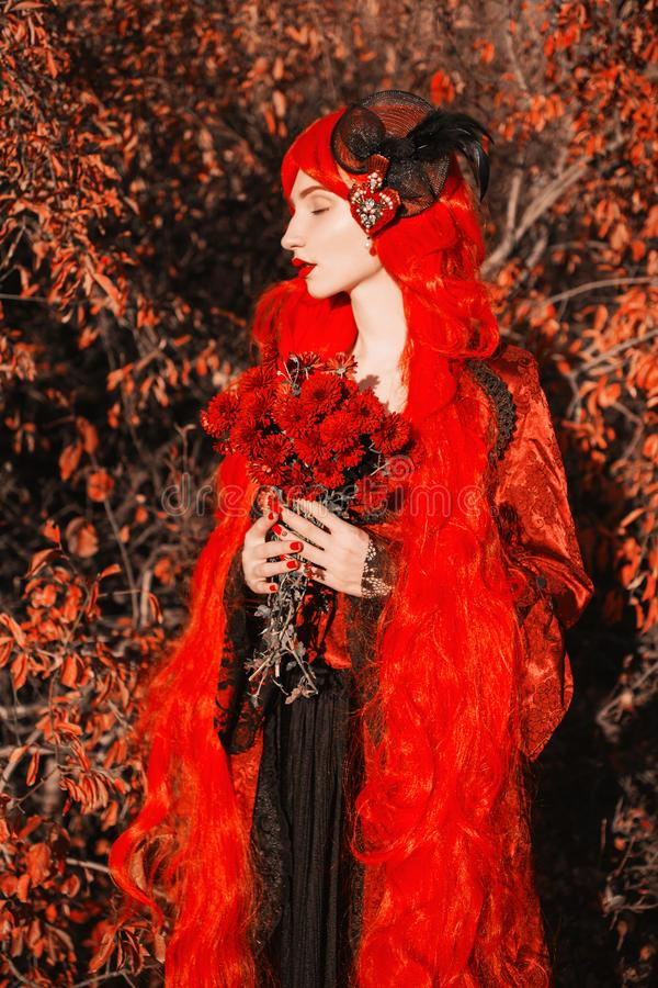 Gothic halloween coat. Young medieval queen with flowers bouquet on autumn background. Lady with red hair. Vampire with pale skin royalty free stock image