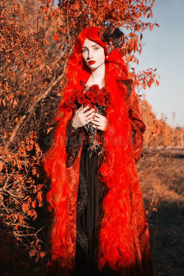 Gothic halloween coat. Young medieval queen hold flower bouquet on autumn background. Lady with red hair. Vampire with pale skin. stock image