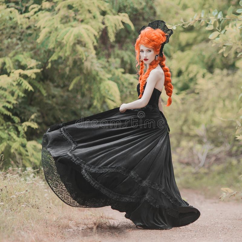 Gothic halloween dress. Young medieval redhead queen with hairstyle. Princess with red hair. Vampire with pale skin. Medieval outfit for halloween party stock photo