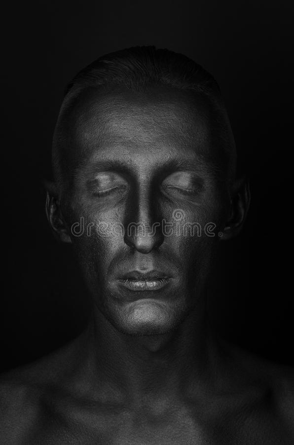 Gothic and Halloween theme: a man with black skin is on a black background in the studio, the Black Death body art. Gothic and Halloween theme: a man with black royalty free stock photography