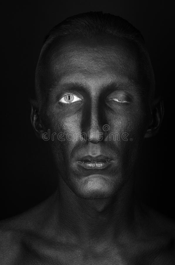 Gothic and Halloween theme: a man with black skin is isolated on a black background in the studio, the Black Death body art. Gothic and Halloween theme: a man royalty free stock images