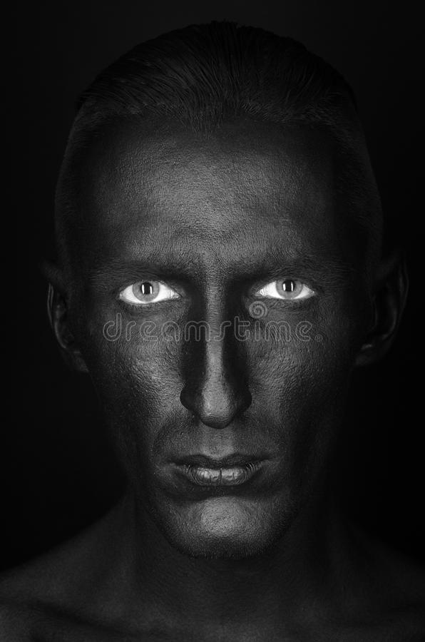 Gothic and Halloween theme: a man with black skin is isolated on a black background in the studio, the Black Death body art. Gothic and Halloween theme: a man royalty free stock photos