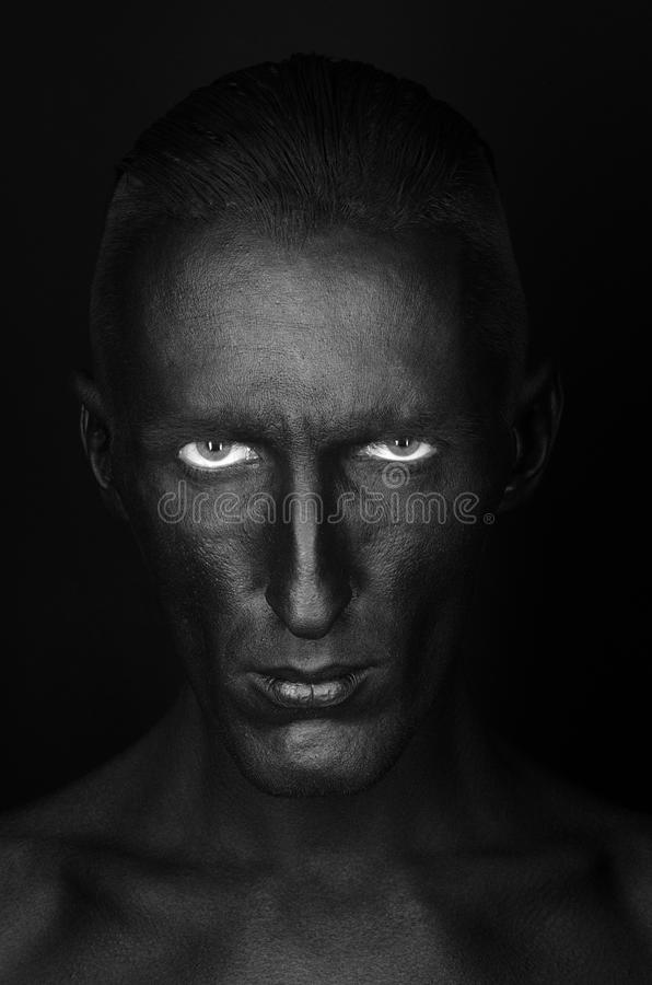Gothic and Halloween theme: a man with black skin is isolated on a black background in the studio, the Black Death body art. Gothic and Halloween theme: a man stock photo