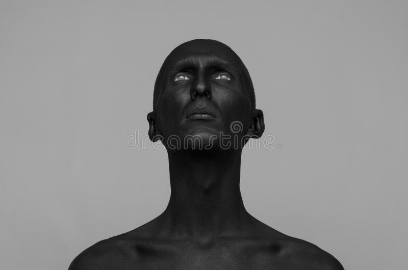 Gothic and Halloween theme: a man with black skin is isolated on a gray background in the studio, the Black Death body art. Gothic and Halloween theme: a man royalty free stock photography